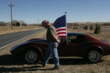 Al Barthelemy, Vietnam veteran (cq) of Loveland waits with his corvette and american flag, both...