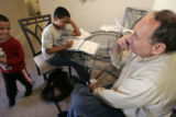 Chuck Kienast helps his grandson, Devon,10 with his homework after school at Kienast's daughter's...