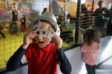 Carson Smail, 7 peers through his Millennium google goggles at the Children's Museum, Denver,...