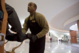 DM0012  Greg Perry shines shoes in the lobby of the Independence Plaza in Denver Tuesday Dec. 16,...