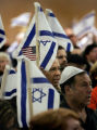 Supporters of Israel wave flags during a speech  at a Community Solidarity Gathering for Israel at...