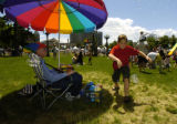 Jerry Williams (cq), left, watches children including 10 year old Chris Orenstein , right, chase...