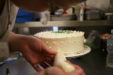 Tanya Gardner, 30 (cq) decorates an italian cream cake with rasberry moose filling while working...