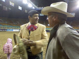 Jerry Diaz left. who brought Catholic Mass to the Stock Show talking to participant Bill Keller  ...