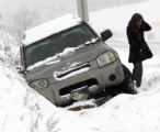 A  woman gets out of her vehicle after sliding into the ditch on westbound I-70 just west of the...
