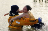 (0479) Samantha Hammerly jumps into the arms of one of the safety officers at the Polar Plunge at...
