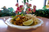 A large plate of Pad Thai for $7.95 sits on a set table at Lao Wang Noodle House 945 S. Federal...