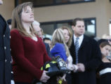 Jennifer Kopp holds her husband Brian helmet with other family members as his casket rolls by at...