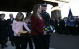 Widow, Jennifer Kopp is escorted outside as her children, Elli and Alan follow behind at the...