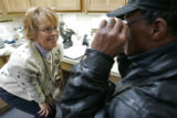 Cherie Yager, who volunteers as an optician 2-3 days a week at the Stout Street Eye Clinic, checks...