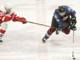 David Jones is defended by Kris Draper, left, in the second period of the Colorado Avalanche...