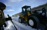 Dave Anderson (cq), left,  watches as Jeremiah Coey (cq) clears snow from around Anderson's...