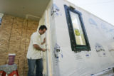 Brad Tomecek (cq) shuts the back door of his pre-fabricated house before it gets hoisted into...