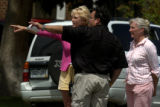 Two women talk to an investigator, center, at a crime scene of a homicide on the 4600 block of...