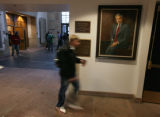 Students walk past a portrait of Bruce Benson in the building named after Bruce Benson - Benson...