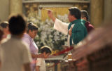 (Center) Father Alejandro Sanchez (cq), of the Cathedral of Mexico City sprinkles holy water on...
