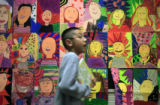 DM0660   Second grader Dominic Saenz passes a wall of self portraits made by students at Valley...