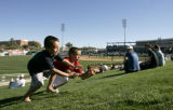 00395 Brothers Diego Guerrero, 7, left, and Carlos Valdez, 10, right, play with a baseball as the...