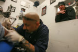 "DM0225   Kyle Anderson watches closely as Luis ""Kartoon"" Guzman works on a tattoo on..."