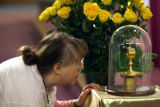 MJM191 Ann Fowles (cq), of Denver, Colo. leans in for a better look at the holy relic of Saint...