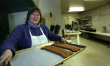 Sue Carroll carries a tray of some of her large dog biscuits-- an all natural product on Monday,...
