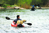 DM0576  A kayaker floats down the South Platte River with his dog near Confluence Park in Denver,...