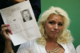 Beth Chapman holds a photo of a fugitive they are looking for in Colorado, as she and her husband...
