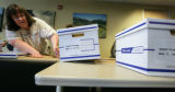 Susan Klinke, temporary election worker adjust one of the 22 boxes delivered to the commission in...