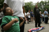 Ajani Chavez (cq), 5, of Denver, left, leans against his father, Mark De La Cruz-Chavez (cq), (not...
