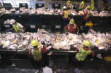 Workers remove unwanted plastic items from paper recycling material for Waste Management of Denver...