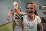 "Molly Casey,13 stands by a life size skeleton in her ""office"" in her home  Wednesday..."