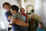 MJM555  Tanya Strickland (cq), left, holds son, Nathan Strickland, 4, as neighbor, Denise Stern...