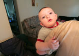 Sean Pattison, 9 months old,  clutches to his mother, Shelli (cq) Pattison's (cq) arm in their...