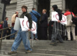 L to R; Brothers Corey(cq)  and Lowell Fulton (cq) carry away protest signs after  a protest...