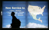 A traveler walks past one of the many advertisements  near the Frontier Airlines ticket counter at...