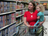 Leslie Shafer (cq) holds her daughter Madison, 2 1/2 as she  shops  at the Wal-Mart in Stapleton ...