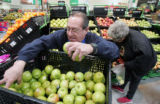 Manny Jiminez  (cq) stocks apples at the Wal-Mart in Stapleton  Friday March 28, 2008. Higher fuel...