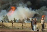 Greg Dickey, right, friends and family stand poised with shovels as a  wildfire rages next to the...