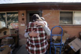 Lonnie Hudson (cq), with her back to the camera, hugs her neighbor Kim DeNeir (cq) as the two...