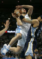 Linas Kleiza is blocked by Andre Brown in the first quarter of the Denver Nuggets against the...