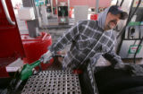 Jose Medina (cq), of Abilene, Tex., looks at the total price as he fills up his truck at Sapp...