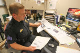 Sgt. Pat Cillo (cq) of the Greenwood Village police department reviews a red light violation in...