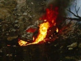 The burning automobile of Timber Dick lays at the bottom of hill along I-70 near highway 40 last...