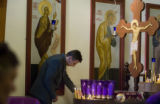 DM0014   Lukic Zeljko lights candles to bless family members who have passed and those who are...