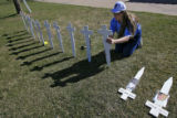 DM6215  Nancy Dzurilla, 38, of Colorado Springs stakes crosses into the ground for the 13 victims...