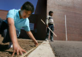 Christopher Acosta (cq), 11, left, measures the area where a garden will be planted at Ellis...
