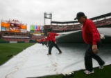 Terry Moll, right, and other members of the gounds crew take the tarp off the field before Opening...