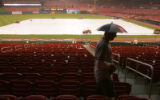 Tracey Winkle (cq), walks through the stands with an umbrella on his head for the Colorado Rockies...