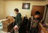 Damien DeNeir (cq), 14, and his friend Cipriano Valentin (cq), 12, pack up Damien's room in the...