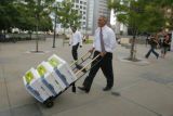 4802  Gov. Bill Ritter wheels a load of petitions out of the Civic Center Plaza after a rally for...